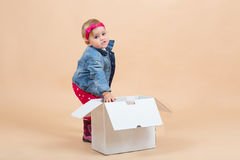 One year baby portrait. Portrait of young cute baby on beige background with white paper box Royalty Free Stock Images