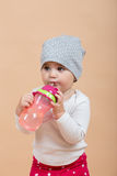 One year baby portrait. Portrait of young cute baby with cap on head on beige background with bottle Stock Images