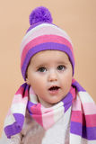 One year baby portrait. Portrait of young cute baby with winter cap and scarf on beige background Stock Photography