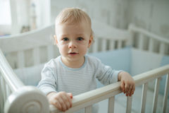 One year baby. Standing in bed portrait. White home interior Stock Images