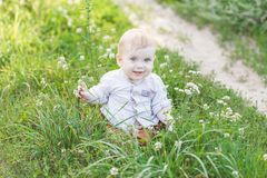 Portrait of cute little blonde boy sitting on the grass royalty free stock photos