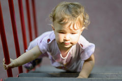 The one-year child climbs up the stairs Stock Image
