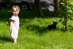 One-year child plays with cat on the lawn Royalty Free Stock Images