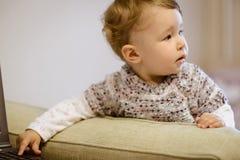 The one-year child secretly clicks on laptop keys Stock Image
