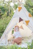 One year cute boy in a teepee outdoors. royalty free stock photography