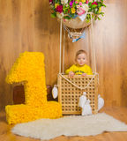 One year next to the basket of the balloon where the baby boy. Closeup of the baby in the basket of the balloon with the number one year Royalty Free Stock Image