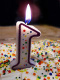 One year old. Number one birthday candle on cake with colorful sprinkles Royalty Free Stock Photos