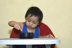 One 1 year old Asian baby boy learning to eat by himself, messy on baby dining chair at home Royalty Free Stock Photos
