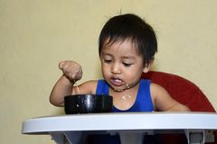 One 1 year old Asian baby boy learning to eat by himself, messy on baby dining chair at home Stock Images