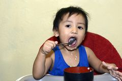 One 1 year old Asian baby boy learning to eat by himself by spoon, messy on baby dining chair royalty free stock image