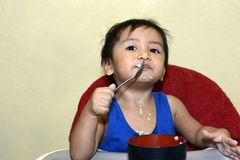One 1 year old Asian baby boy learning to eat by himself by spoon, messy on baby dining chair stock image