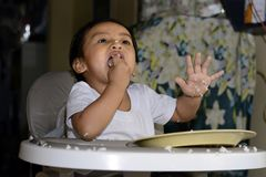 One 1 year old Asian baby boy learning to eat by himself by spoon, messy on baby dining chair at home Stock Photos