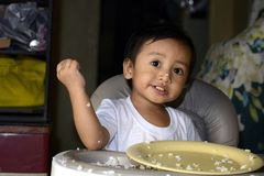 One 1 year old Asian baby boy learning to eat by himself by spoon, messy on baby dining chair stock photo