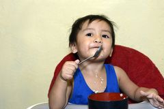 One 1 year old Asian baby boy learning to eat by himself by spoon, messy on baby dining chair stock photos