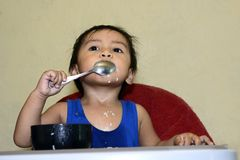 One 1 year old Asian baby boy learning to eat by himself by spoon, messy on baby dining chair at home Royalty Free Stock Photography