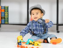 One year old Asian baby boy sitting on floor playing with toy. One year old Asian baby boy smile and sitting on floor holding to the magnifying glass play the royalty free stock photo