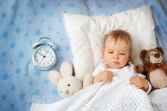 One year old baby with alarm clock Stock Photos