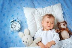 One year old baby with alarm clock Stock Photo