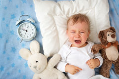 One year old baby with alarm clock Stock Image