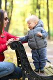 One year old baby boy in autumn park with his mother Royalty Free Stock Images
