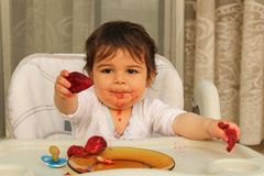 One year old baby boy eating strawberryes and offering to share stock images