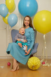 One year old baby boy first birthday. Toddler child with mother sitting in chair. And having fun with balloons stock photo