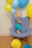 One year old baby boy first birthday. Toddler child sitting in chair. One year old baby boy first birthday. Toddler child sitting in chair and having fun with royalty free stock image