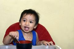 One 1 year old baby boy learning to eat alone smiling happy but messy Royalty Free Stock Images