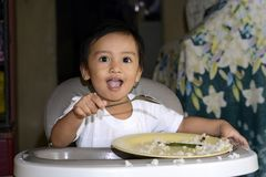 One 1 year old baby boy learning to eat alone smiling happy but messy on baby dining chair at home Stock Photo