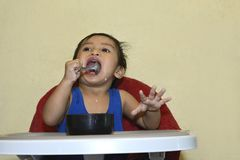 One 1 year old baby boy learning to eat alone smiling happy but messy Royalty Free Stock Photo