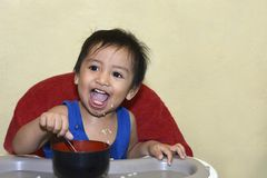 One 1 year old baby boy learning to eat alone smiling happy but messy Stock Image