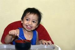 One 1 year old baby boy learning to eat alone smiling happy but messy Stock Photo
