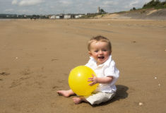 One year old baby boy playing with a football on the beach. In summer Royalty Free Stock Image
