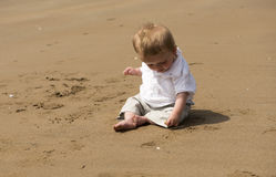 One year old baby boy playing with sand on the beach. In summer Royalty Free Stock Photo