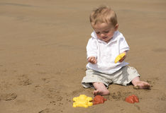 One year old baby boy playing with sand on the beach. In summer Stock Photo