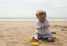 One year old baby boy playing with sand on the beach. In summer Royalty Free Stock Photos