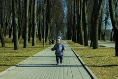 A one year old baby boy taking some of his first steps outdoors in spring park. Cute toddler walking in the green forest stock images