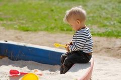 One year old baby boy toddler at playground sandbox Stock Photo