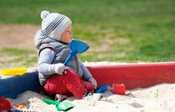 One year old baby boy toddler at playground sandbox Stock Photos