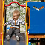One year old baby boy toddler at playground slide. Portrait of toddler child outdoors. One year old baby boy at playground slide Royalty Free Stock Photography