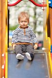 One year old baby boy toddler at playground slide. Portrait of toddler child outdoors. One year old baby boy at playground slide Royalty Free Stock Image