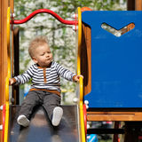 One year old baby boy toddler at playground slide. Portrait of toddler child outdoors. One year old baby boy at playground slide Stock Image