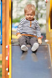 One year old baby boy toddler at playground slide. Portrait of toddler child outdoors. One year old baby boy at playground slide Stock Photos