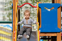 One year old baby boy toddler at playground slide. Portrait of toddler child outdoors. One year old baby boy at playground slide Royalty Free Stock Photos