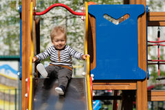 One year old baby boy toddler at playground slide Stock Image