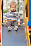 One year old baby boy toddler at playground slide Royalty Free Stock Image