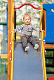 One year old baby boy toddler at playground slide. Portrait of toddler child outdoors. One year old baby boy at playground slide Royalty Free Stock Photo