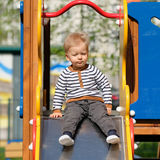 One year old baby boy toddler at playground slide. Portrait of toddler child outdoors. One year old baby boy at playground slide Royalty Free Stock Images