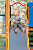 One year old baby boy toddler at playground slide. Portrait of toddler child outdoors. One year old baby boy at playground slide Stock Images