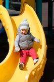 One year old baby boy toddler at playground slide. Portrait of toddler child wearing vest jacket outdoors. One year old baby boy at playground slide Stock Photography